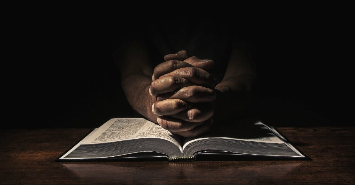 a praying hand and Bible